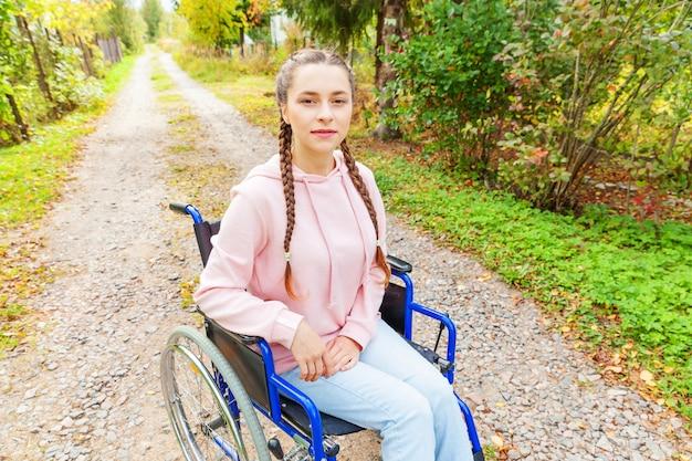 Mulher feliz nova da desvantagem na cadeira de rodas na estrada no parque do hospital que espera serviços pacientes. menina paralisada na cadeira inválida para pessoas com deficiência ao ar livre na natureza. conceito de reabilitação.
