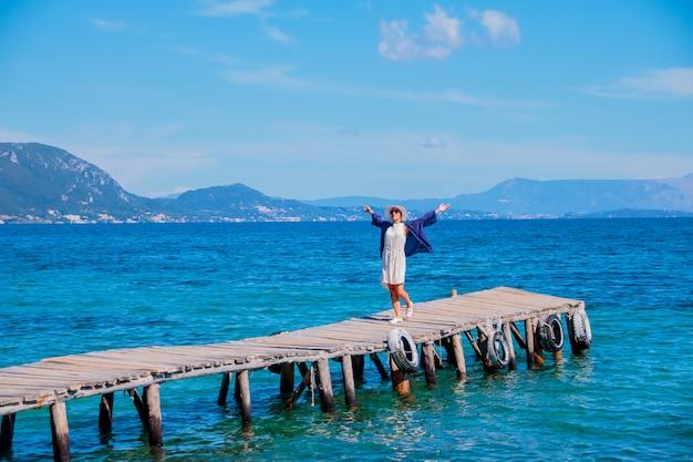 Mulher feliz nova na ponte perto do mar, horas de verão, conceito das férias felizes.