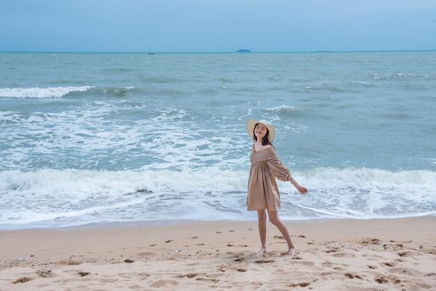 Mulher feliz nova que anda na praia com apreciação e feliz