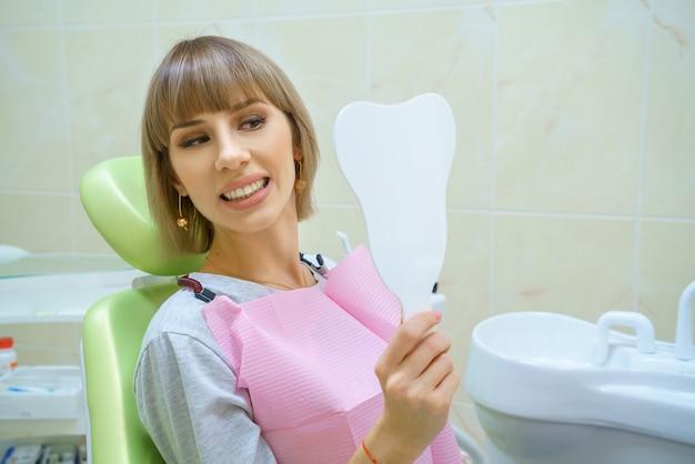 Mulher feliz nova que senta-se no escritório do dentista, dentes saudáveis.