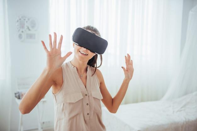 Mulher feliz obtém experiência com o uso de headset de realidade virtual de óculos vr em um ambiente brilhante