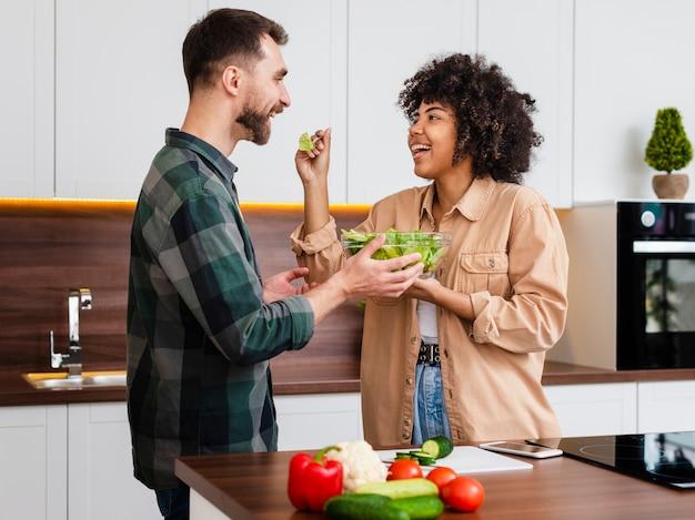 Mulher feliz oferecendo salada para o namorado