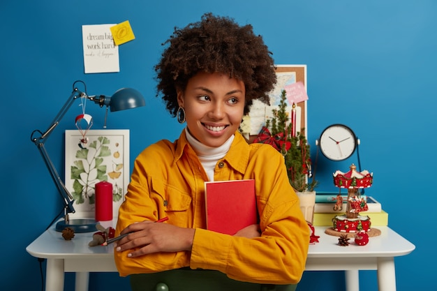 Mulher feliz olha pensativamente para o lado, sorri amplamente, segura uma carteira vermelha e um lápis para fazer anotações