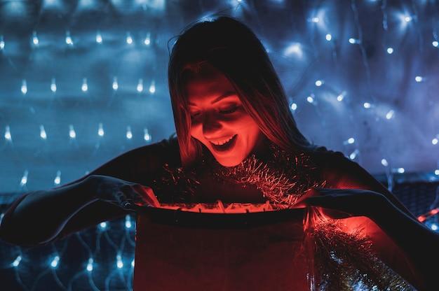 Mulher feliz olhando as lâmpadas brilhantes