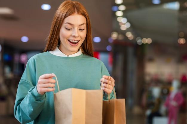 Mulher feliz olhando em uma sacola de compras