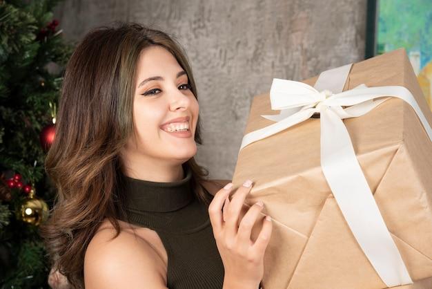 Mulher feliz olhando os presentes de natal na frente de uma árvore de pinha