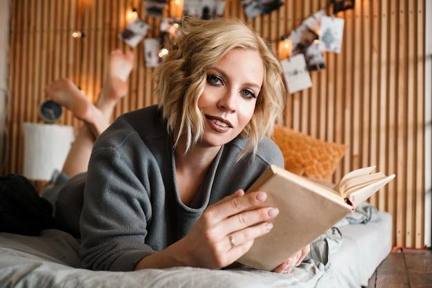 Mulher feliz olhando para a câmera, relaxando e lendo um livro na cama aconchegante - parede de madeira e fotos com luzes - fundo desfocado