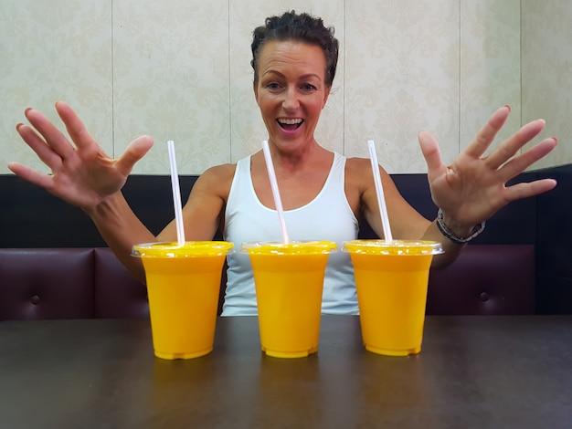 Mulher feliz olhando para a manga lassi bebida dentro de um restaurante indiano, com os braços erguidos