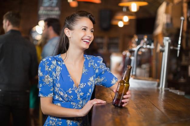 Mulher feliz olhando para longe enquanto segura uma garrafa de cerveja