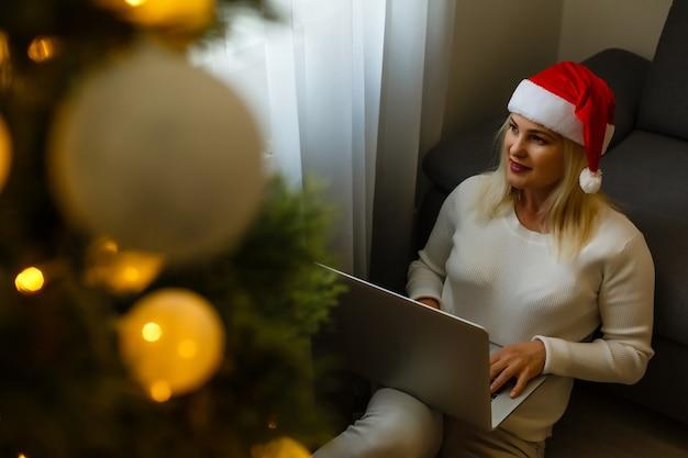 Mulher feliz olhando para um laptop na frente da árvore de natal