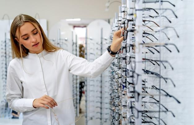 Mulher feliz optometrista, oculista está de pé com muitos óculos