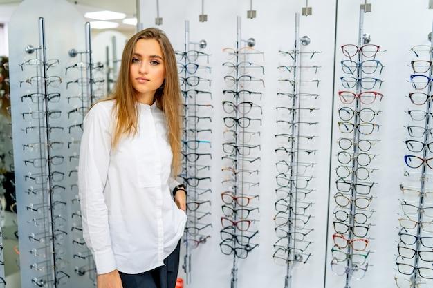 Mulher feliz optometrista, oculista está em pé com um conjunto de óculos