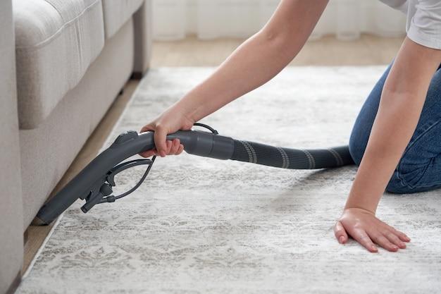 Mulher feliz ou dona de casa com aspirador de pó limpando o chão debaixo do sofá em casa
