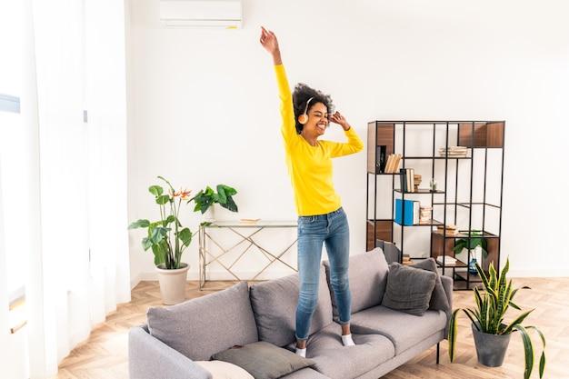 Mulher feliz ouvindo música pulando e dançando no sofá em casa