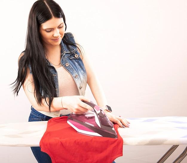 Mulher feliz passando roupas com ferro elétrico isolado