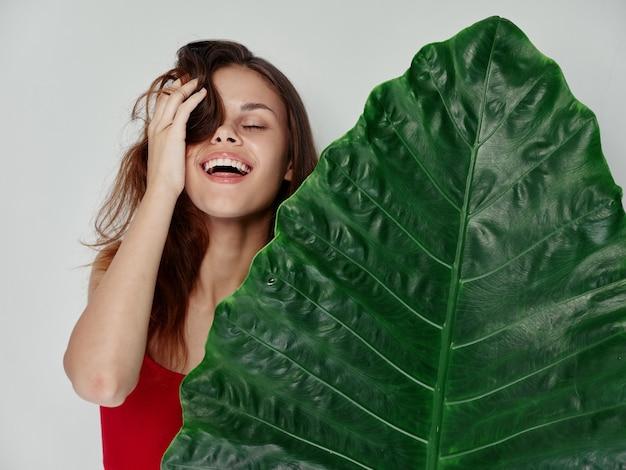 Mulher feliz pele limpa folha verde palmeira. foto de alta qualidade