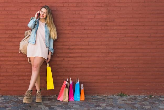 Mulher feliz perto de sacos de compras, falando por telefone