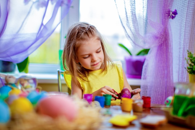 Mulher feliz pintando ovos de páscoa, criança pequena em casa se divertir. feriado de primavera
