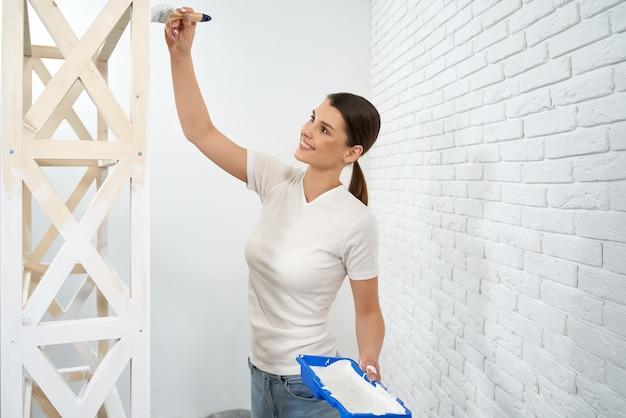 Mulher feliz pintando prateleiras de madeira em casa