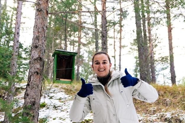 Mulher feliz porque acabou de colocar um ninho de pássaro de madeira na floresta. paisagem de neve