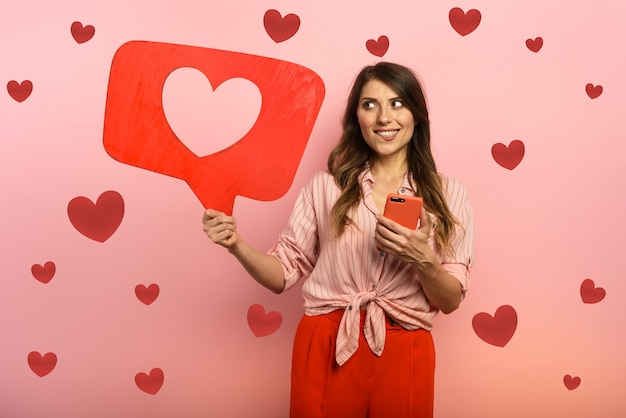 Mulher feliz porque recebe corações no aplicativo de mídia social