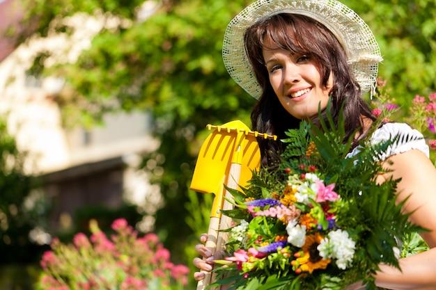 Mulher feliz posando com ferramentas de jardinagem e flores