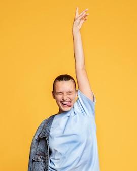 Mulher feliz posando com jaqueta jeans e língua de fora
