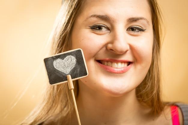 Mulher feliz posando com uma pequena lousa com coração desenhado