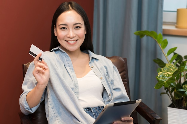 Mulher feliz posando enquanto segura o cartão de crédito e tablet