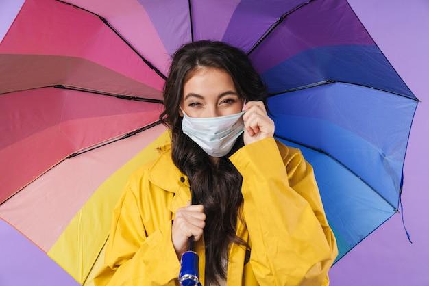 Mulher feliz positiva em capa de chuva amarela posando isolado sobre a parede roxa segurando guarda-chuva usando máscara médica.