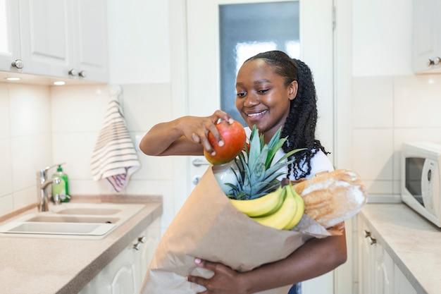 Mulher feliz positiva saudável segurando uma sacola de papel cheia de frutas e legumes. jovem mulher segurando uma sacola de compras de supermercado com legumes, em pé na cozinha