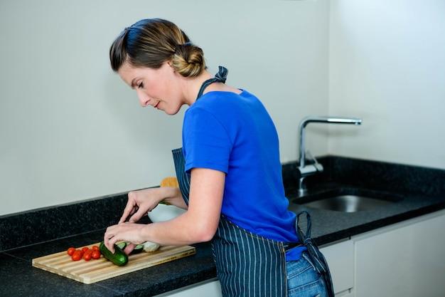 Mulher feliz preparando alguns legumes na cozinha