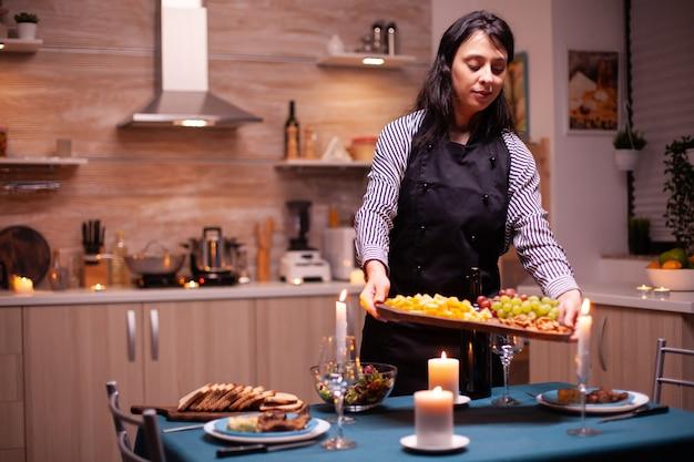Mulher feliz preparando um jantar romântico e segurando a placa com uvas e queijo na sala de jantar. jovem senhora caucasiana cozinhando para o marido um jantar romântico, esperando na cozinha.