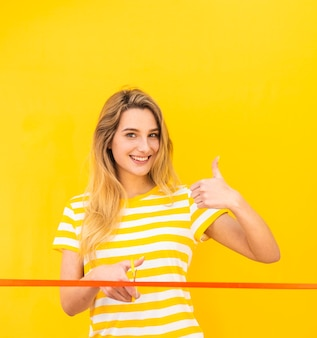 Mulher feliz pronta para cortar a fita vermelha