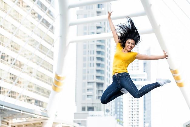 Mulher feliz pulando com as mãos estendidas na cidade