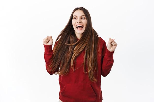 Mulher feliz pulando de alegria e triunfo, atingir meta de sucesso, olhando para o lado e gritando de felicidade, comemorar a vitória, ganhando algo, parede branca