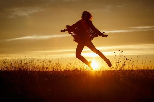 Mulher feliz pulando no campo ao pôr do sol