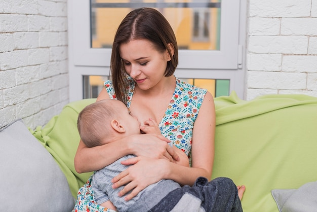 Mulher feliz que amamenta seu filho