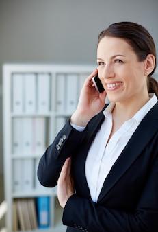 Mulher feliz que fala no telefone