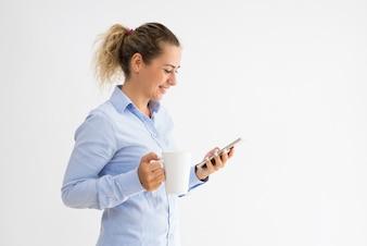 Mulher feliz que guarda a caneca e que lê a mensagem no smartphone