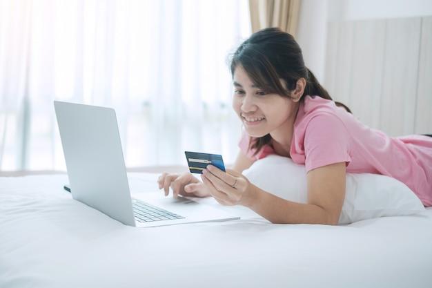 Mulher feliz que guarda o cartão de crédito e que usa o computador portátil para compras on-line ao fazer pedidos na cama na manhã em casa.