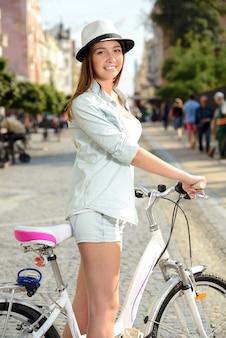 Mulher feliz que monta uma bicicleta na rua na cidade.