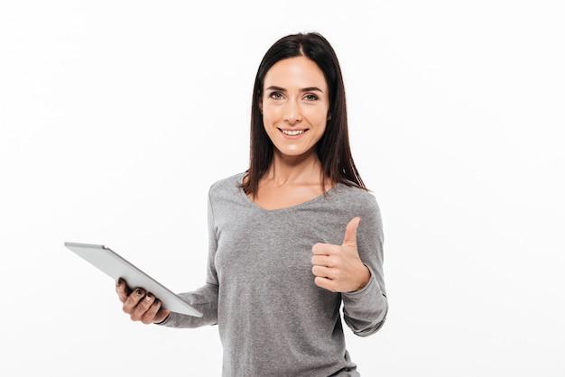 Mulher feliz que mostra os polegares acima usando o tablet pc.