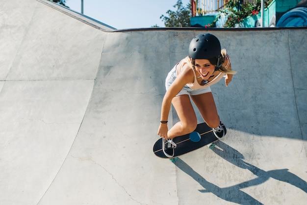 Mulher feliz que patina com capacete