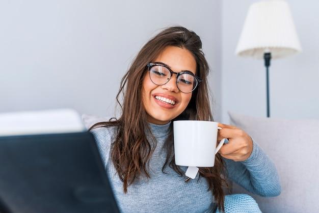 Mulher feliz que relaxa em casa no inverno acolhedor ou no fim de semana do outono com livro e copo do chá quente