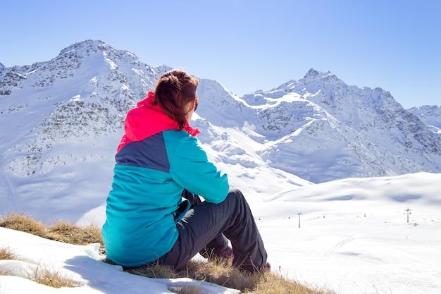 Mulher feliz que relaxa no topo da montanha sob o céu azul com luz solar no dia de inverno ensolarado, férias, viagens, montanhas da paisagem.