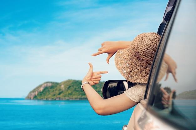 Mulher feliz que senta-se na estação de verão do carro e da viagem no dia de descanso e especial do mar a vacation.