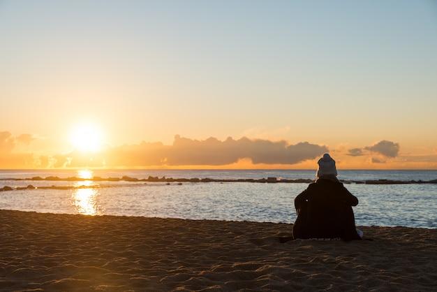 Mulher feliz que senta-se na praia fria com o copo do chá com luzes no por do sol em barcelona, espanha.