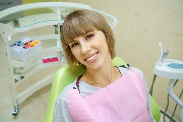 Mulher feliz que senta-se no escritório do dentista, dentes saudáveis.