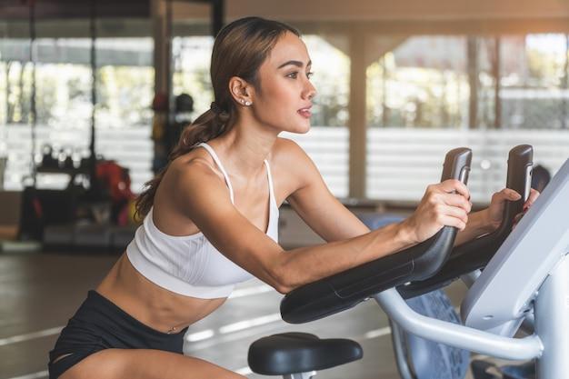Mulher feliz que sorri durante o exercício na máquina da bicicleta no clube de esporte do gym.